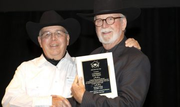 Two men shaking hands one accepting award