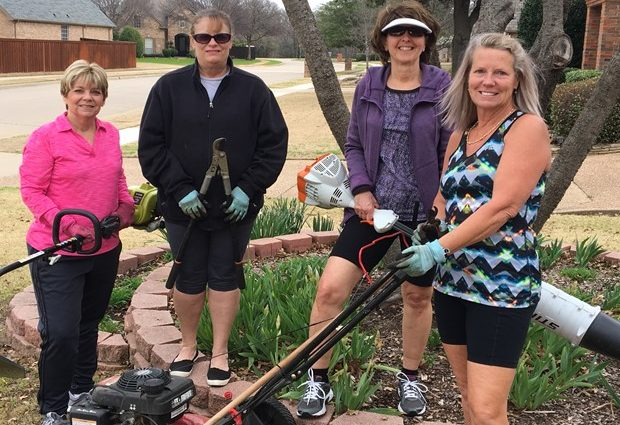 Four women standing in yard holding lawn tools