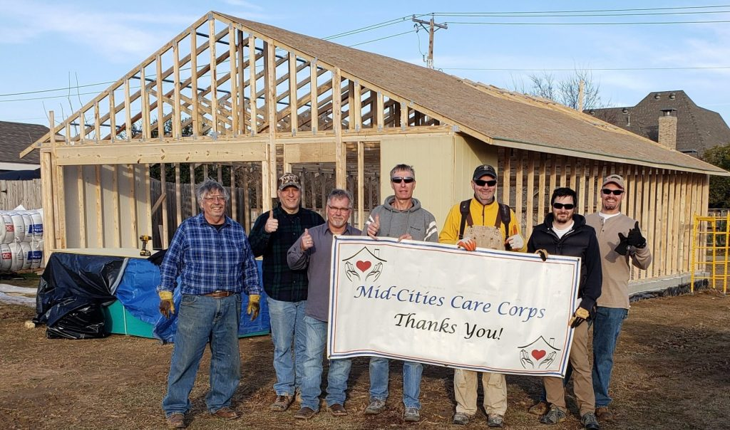 Volunteers standing in front of nearly finished storage shed for MCCC